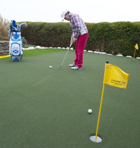 Image caption: Catriona Matthew MBE practises putting on her new 375 square feet (114 square metre) Huxley Premier Putting and Chipping Green