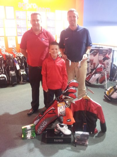 Adam and his Dad Colin (blue shirt) are pictured with their prize at the american golf store in Belfast