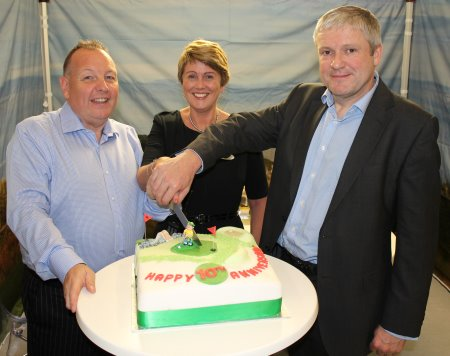 TGI Golf Managing Director Eddie Reid (left) cuts at commemorative 10th anniversary cake presented to the group by Harrogate International Centre Director Simon Kent (right) and Deborah Rolph, HIC Event Planner (centre).