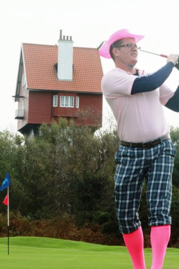 Stephen Cordory, Operations Manager, Thorpeness Hotel and Golf Club, tees off in front of Suffolk's iconic House in the Clouds during the Thorpeness Pink Putter