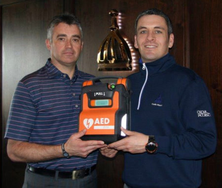 Donnie Ross, deputy golf operations manager at Castle Stuart Golf Links and a qualified Heartstart trainer (left) receives the defibrillator from Jeremy Matte, the club's director of golf.