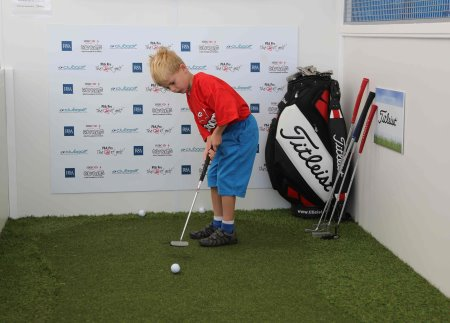 A young golfer concentrating hard on the putting challenge supported by Titleist
