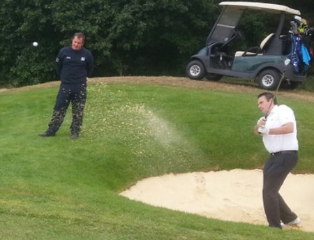 Birchwood Park Golf Centre Head Professional Stephen Lee plays from the remodeled bunker on hole eight of the Main Course with course manager Mark Bell watching