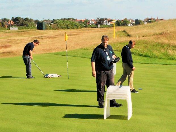 Karl McMullan, Christian Spring, Richard Windows taking measurements on 12th green at Royal Liverpool