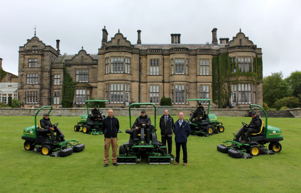 Matfen Hall Golf Club course manager Derek Millar, John Deere territory manager Richard Charleton and Greenlay dealer principal Geoff Lowes (standing, left to right) with the greenkeeping staff and their new John Deere fleet in front of the Grade II listed 19th century country mansion.