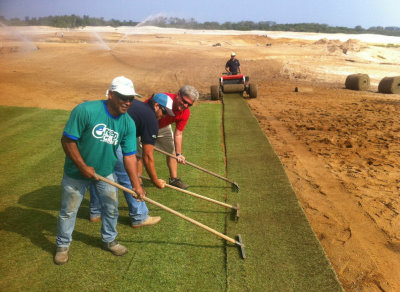 Big Roll installation: Green Grass crew members, Fabricio installing and Renato and Israel (front ) with David Doguet of Bladerunner Farms pulling the sod into place (photo courtesy Marcelo Matte, Green Grass Brazil)