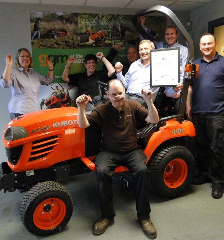 Chris Gibson (sitting) and some of the team celebrate the award