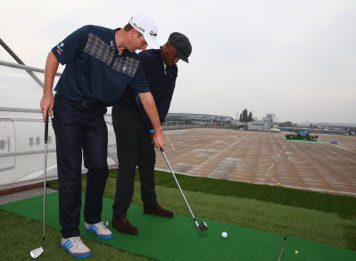 Justin Rose coaches Ian Wright to play a shot from the wing of a British Airways Boeing 747