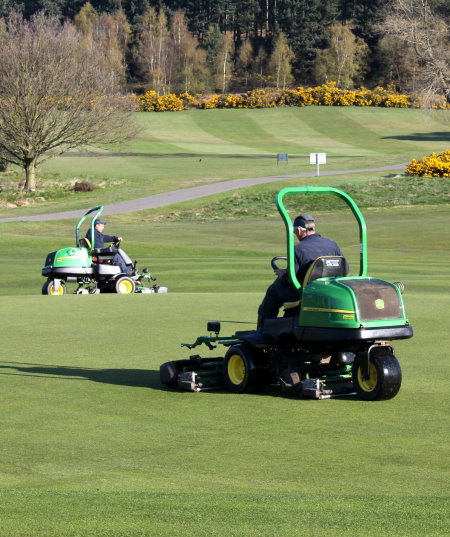 Two of the John Deere 2500E electric hybrid greens mowers at work on this traditional heathland course, which features heather, fern, gorse and pine in abundance.