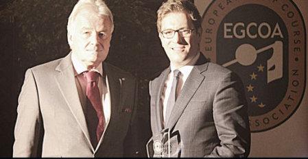 Ian Randell holds the award that has just been presented by Alexander Baron von Spoercken