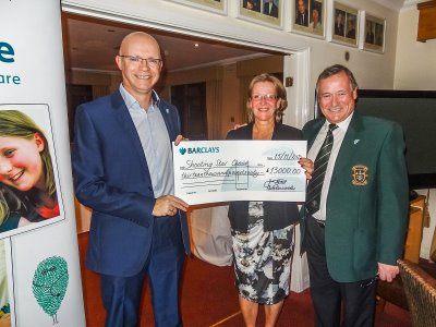 Shooting Star Chase's Mike Hey (left) receives the cheque from Pyrford Golf Club Captains Tuula Kaminarides and John Gilkes