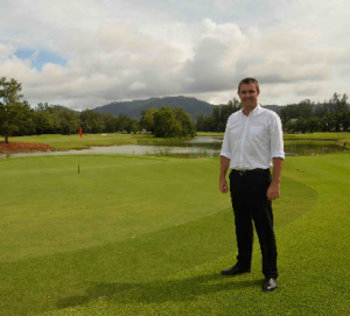 Laguna Phuket's director of golf, Paul Wilson, beside the 8th green with Phuket's iconic mountains in the background