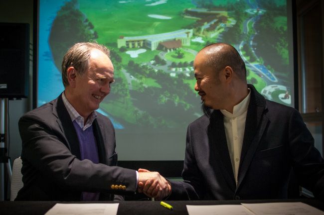 Euan Loudon and Han Zi Ding shake hands after signing agreement