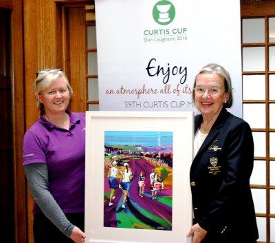 Lucy (left) presenting the original artwork to Liz Jordan, Lady Captain of Dun Laoghaire G.C