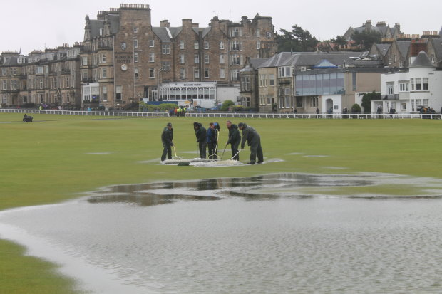 The home greenkeeping team clearing water from the 18th on Friday morning
