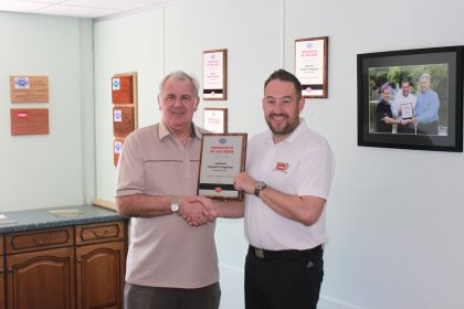 Topturf Irrigation MD Colin Clarke on the left is presented his award by Roger Lupton, Lely's former Otterbine sales manager
