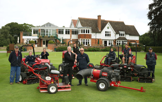 Course manager Sid Arrowsmith shakes hands with Lely's Robert Rees, left, in front of the club's new Toro machines and members of the greenkeeping team