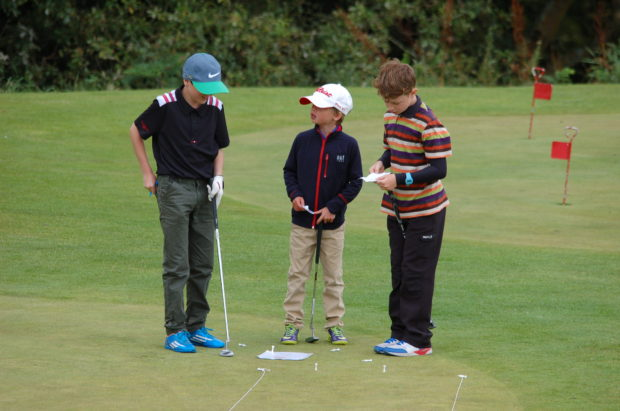 Three young players weigh up their options on the practice putting green at Houghwood Golf Club at the end of season competition for players on the under 14 coaching programme
