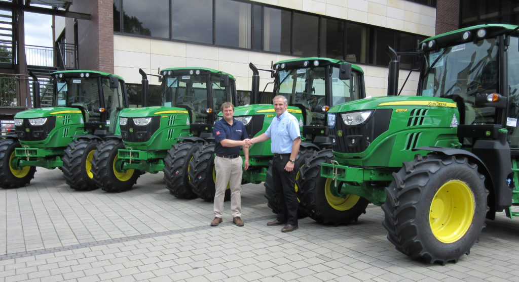 Adrian Abbott (left) of MJ Abbott Limited and Jamie Fisher of dealer R Hunt Ltd with the new John Deere 6120M tractor fleet during the handover at the Mannheim tractor factory in Germany.